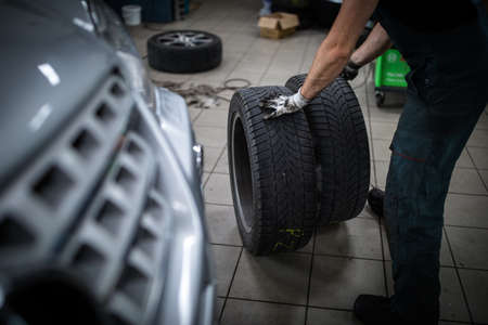 Car mechanic changind tires of a car in a repair shop/car garage (shallow DOF/color toned image)