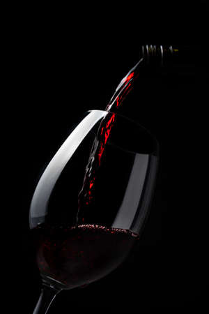 Red wine pouring into wine glass on dark background - lovely, rich, full bodied, ruby coloured, Shiraz
