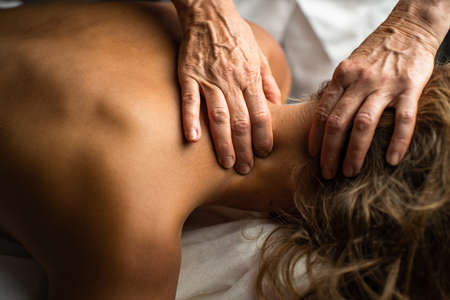 Massage procedure - neck and whole body massage by a female masseuse. doing massaging using oil. neck and whole body massage, relaxing massage, strong hands of a masseur, massage to increase work efficiency