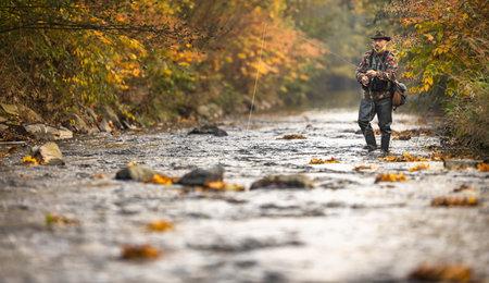 Fly fisherman fly fishing on a splendid mountain river Archivio Fotografico