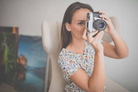 Pretty, young female photographer in her studio taking photos with a vintage film camera (color toned image)