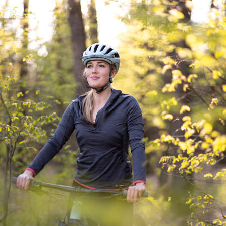 Pretty, young woman with her mountain bike going for a ride past the city limits, getting her dose of daily cardio