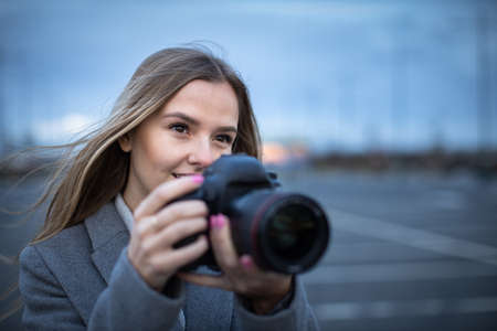 Pretty, young woman taking photos with her professional dslr camera Archivio Fotografico
