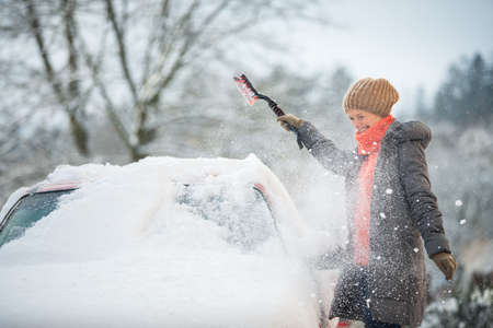 Pretty, young woman cleaning her car from snow after heavy snowstorm (color toned image)