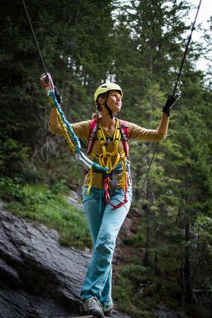 Pretty, female climber on a via ferrata - climbing on a rock in Swiss Alps Archivio Fotografico