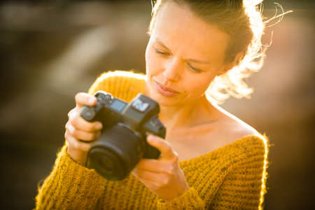 Hobby photographer concept. Outdoor lifestyle portrait of young woman taking photos with her mirrorless camera in warm evening sunlight