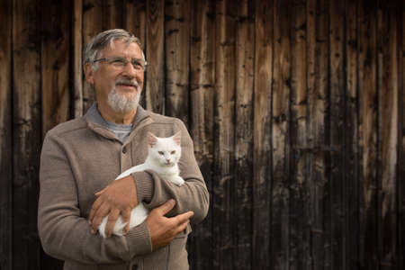 An elderly man holds a cute white kitten and smiles to the camera, selective focus, plenty of copy space