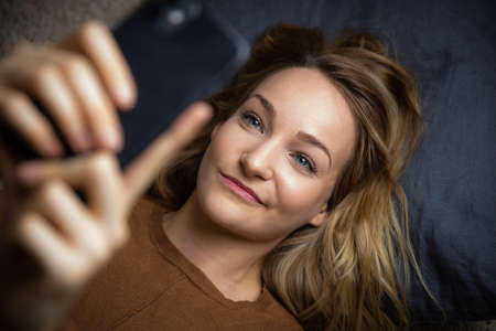 Pretty, young woman using her smart phone at home Archivio Fotografico
