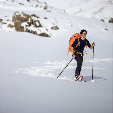 Winter sports - young man walking with snowshoes in high mountains covered with lots of snow (selective focus on the mountain in the background)