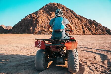 A Bedouin on an All-terrain vehicle er the dunes of the red  Egyptian desert