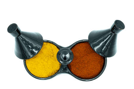 A two-compartment tajine top view spice rack with red paprika and turmeric, perfect for services or commercials on healthy Indian or Moroccan cuisine
