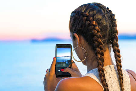 A girl with braids contemplates the sunset making a shot with her smartphone