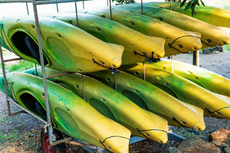 A set of ten old and worn kayak of various color.