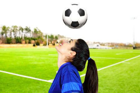 A young soccer champion trains by dribbling on the pitch. Subject on a blurred background. Perfect shot for emancipation, women's sports and women.