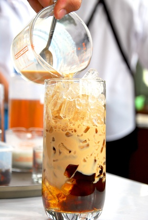 coffee jelly: Coffee is being poured onto a glass with ices and coffee jelly Stock Photo