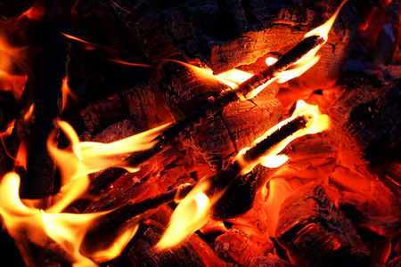 Glowing embers in hot red color, abstract background. The hot embers of burning wood log fire. Firewood burning on grill.