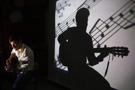 The guitar player is singing the song with a shadow of notes and silhouette of the guitarist on the background