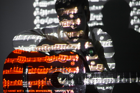Portrait of the bearded guitar player with projection of the notes. Manis holding his guitar and looking into the camera Stock Photo