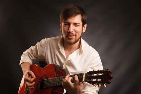 Young musician is playing acoustic guitar and singing, on dark background