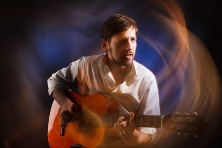 Portrait of the soul of the musician who is playing acoustic guitar and singing emotional song. Famous bard