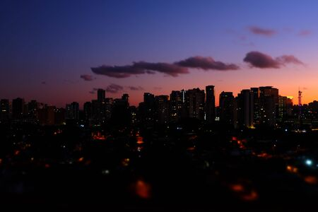 Flat cityscape with pink sky, white clouds and sunset or sunrise. Modern city skyline flat panoramic background. Urban city tower skyline illustration