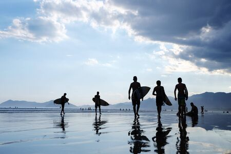 Silhouettes of unrecognizable surfers carrying their surfboard on sunset beach, with a cloud and mirroring in the water and mountains in the background Standard-Bild