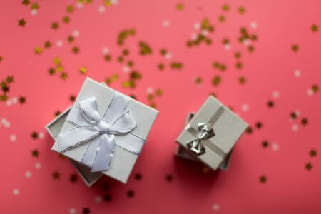 White textured gift boxes with ribbon bows surrounded by stars and snowflakes on a coral background, from above..
