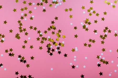 Stars and snowflakes on a pink background, from above..