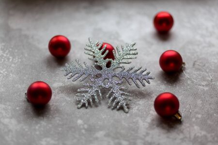 Christmas decorations on a gray background. A silver snowflake surrounded by unfocused burgundy Christmas balls, Christmas toys and stone ornament. Top view.. Banco de Imagens