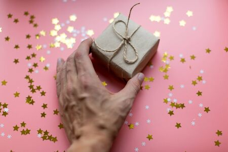 Mans hand taking a craft textured gift box with ribbon bow surrounded by stars and snowflakes on a coral background, from above