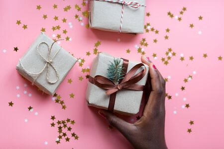 African womans hand taking a craft textured gift box with ribbon bow surrounded by stars and snowflakes on a coral background, from above