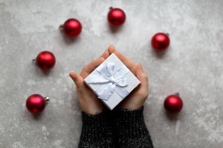 Womans hand is taking a craft textured gift box with ribbon bow by unfocused vinous Christmas balls on a gray background, from above.. Banco de Imagens