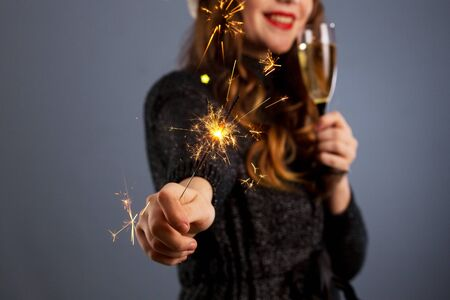 Attractive cheerful girl with curly hair in Christmas hat smiling, holding sparkler and drinking champagne, isolated on gray background..