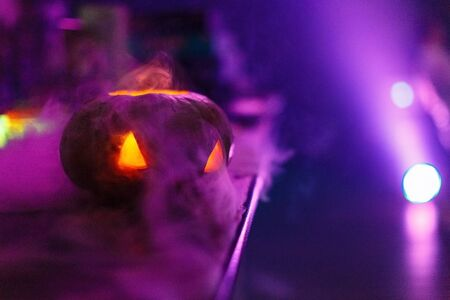 Halloween pumpkin face lantern at night with misty smoke. Halloween background.