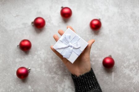 Womans hand is holding a craft textured gift box with ribbon bow by unfocused vinous Christmas balls on a gray background, from above..
