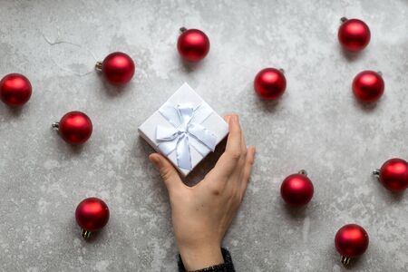 Woman's hand is taking a craft textured gift box with ribbon bow by unfocused vinous Christmas balls on a gray background, from above.. Imagens