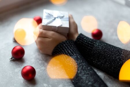 Woman's hands are holding a craft textured gift box with ribbon bow by unfocused vinous Christmas balls on a gray background, from above..