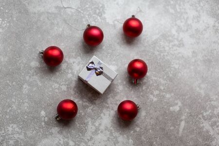 White gift box with white ribbon bow and vinous christmas balls around, isolated on gray background..