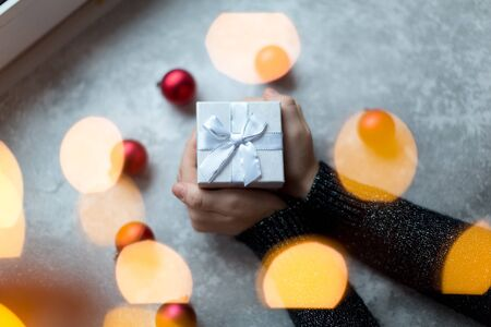 Womans hands are holding a craft textured gift box with ribbon bow by unfocused vinous Christmas balls on a gray background, from above.. Banco de Imagens
