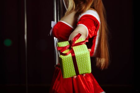 Happy caucasian Santa Woman is smiling and holding Gift Box for Christmas or New Year. Holiday concept. Isolated on gray background.. 写真素材