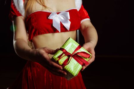 Picture of cheerful santa helper strip-tease girl with many gifts box dancing near pylon isolated on black background..