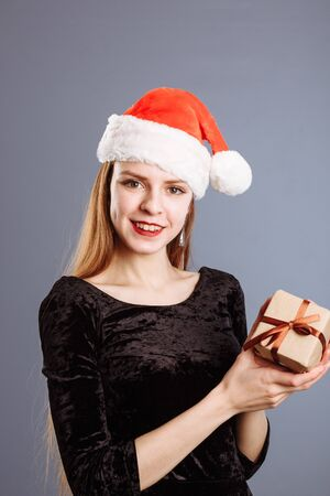 Young caucasian lady in a red christmas hat and black dress is giving a gift box to you to me on gray background. isolated