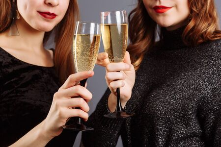 Beautiful glasses of champagne in womens hands. Ladies Look and smile into the camera, isolated on gray background..