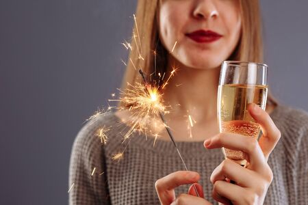 Attractive cheerful lovely girl with long light hair smiling, holding Bengal light and drinking champagne, isolated on gray background..