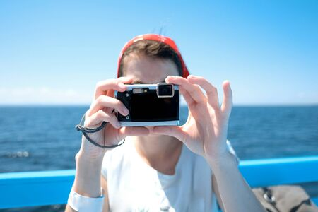 Unrecognizible Woman taking photo with waterproof camera on the beach. Happy girl on vacation taking picture on sea background.