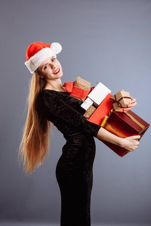 Picture of cheerful Santa helper girl in a sexy dress with many gifts box smiling posing and looking into the camera isolated