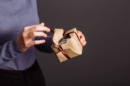 Image of happy girl opening and looking into gift box and wondering..