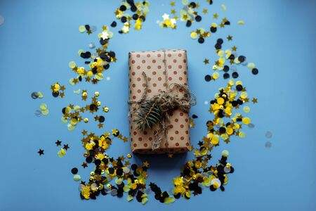 White textured gift boxes with ribbon bows surrounded by stars and confetti on a blue background, from above.. 写真素材