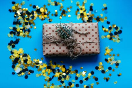 Present box with craft brown bow on blue background with yellow black confetti. Flat lay style. Christmas and new year concept..