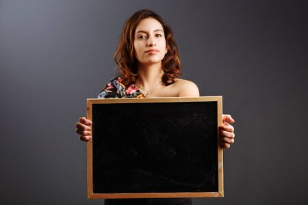 portrait of young latin american woman student holding a empty chalkboard isolated on gray